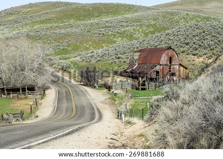 Winding country road and rusty barn - stock photo