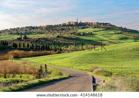 Winding country road meandering up hills to the old town of Pienza with green grassy meadows on the hillside under sunny sky ~ Beautiful spring scenery of idyllic Tuscany countryside in northern Italy - stock photo