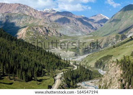 Winding dirt road going to Kumtor gold mine through Sary-Moinok pass. Kyrgyzstan - stock photo