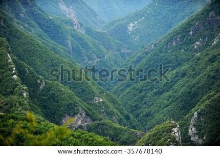 Winding dirt road in albanian mountainous Theth region - stock photo