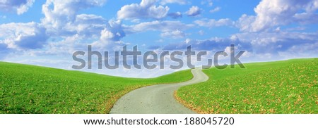 winding hiking trail and cloudy blue sky - stock photo