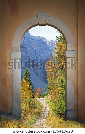 winding hiking trail through arched door, mountainous autumn landscape.