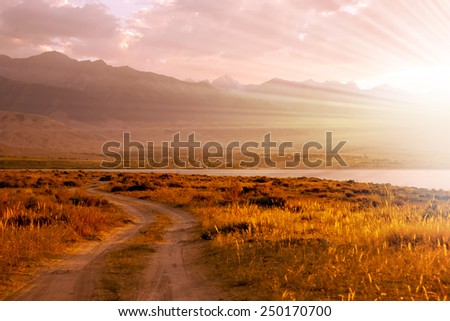 Winding patway at the shore of a mountain lake - stock photo