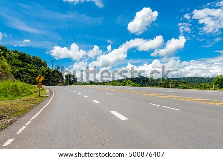Winding Paved Road with blue sky in the mountain.