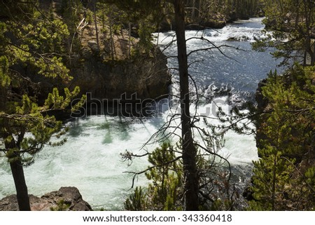 Winding rapids and cliffs with pine trees above Upper Falls of the Yellowstone River in Yellowstone National Park, Wyoming. - stock photo