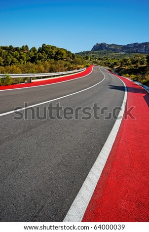Winding Road and Red Cycle Lane through mountains. Road from Benidorm to Guadalest. Clear blue sky. Converted from RAW - stock photo