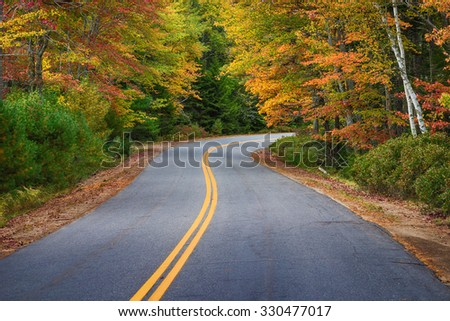 Winding road curves through colorful autumn trees in New England