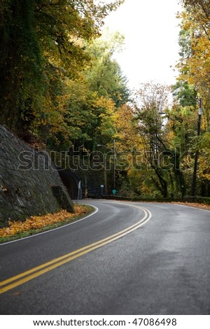 Winding road going to tunnel daytime - stock photo