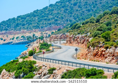 winding road in the mountains leads to the sea - stock photo