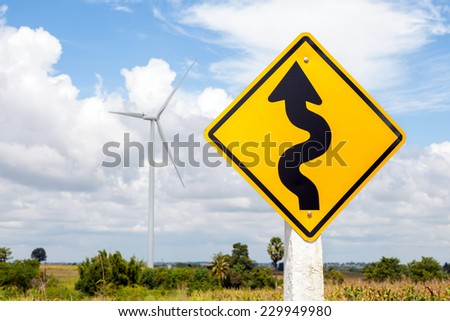 Winding road sign and windmill background in wind farm, Korat province in Thailand. - stock photo