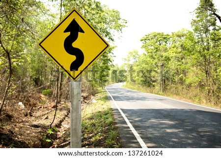 Winding road sign in the forest and mountain - stock photo