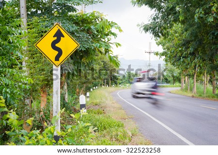 Winding road sign in the forest with blurred car and motorcycle. - stock photo