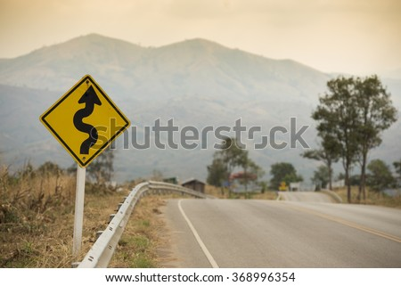 Winding Road Sign on asphalt road - stock photo