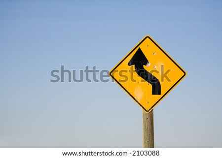 winding road sign with bullet holes - turbulent times ahead, dangerous future. - stock photo