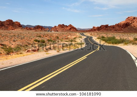 Winding road through desert - stock photo