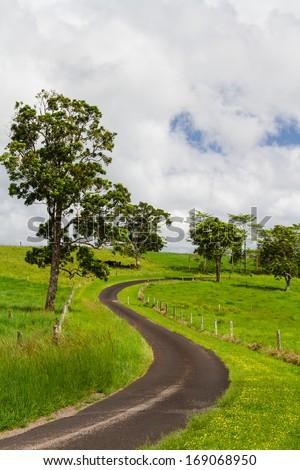 Winding road through farmlands in Queensland, Australia - stock photo