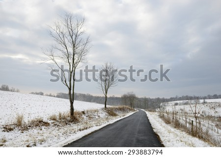 Winding Road Through Snowy Rural Fields - stock photo