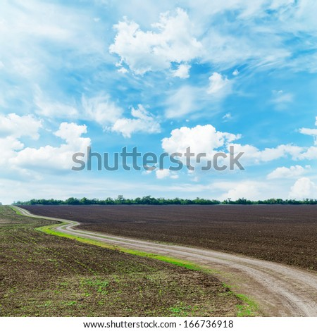 winding rural road under dramatic sky - stock photo