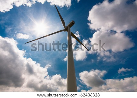 Windmill against a blue sky and clouds, alternative energy source - stock photo