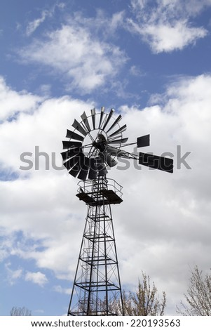 Windmill against blue cloudy sky