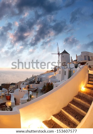 Windmill against colorful sunset, Santorini island in  Greece