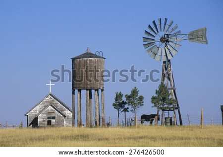 Windmill and abandoned prairie church, WY - stock photo