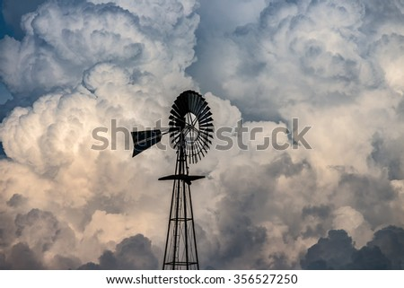 Windmill and dramatic clouds, rural America - stock photo