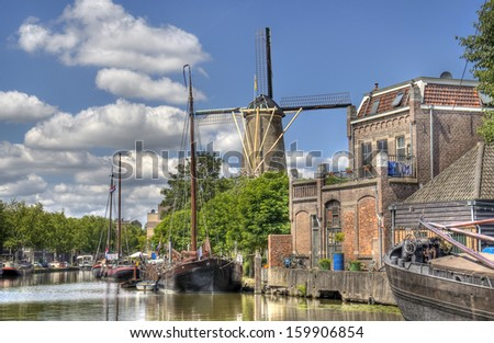 Windmill and historical boats in a canal in Gouda, Holland - stock photo