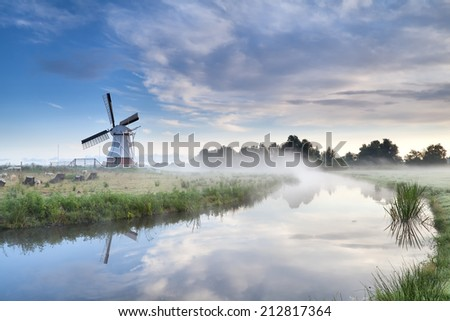 windmill and river in foggy morning, Netherlands - stock photo