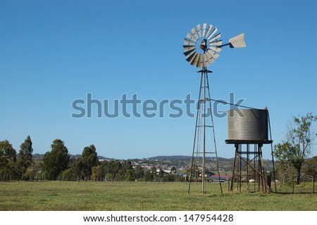 Windmill and tankstand in paddock, Queensland, Australia. Windmills are commonly used for pumping water from bores or dams to troughs for livestock. - stock photo