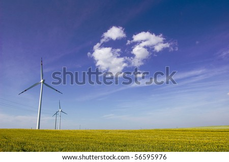 Windmill conceptual image. Windmills on the green field. - stock photo