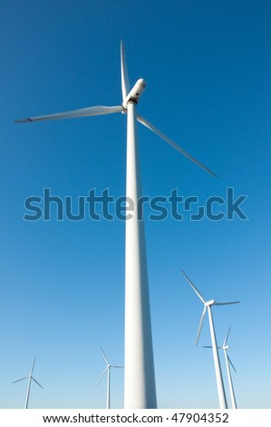 Windmill farm shot with wide angle on sunny day, vertical - stock photo