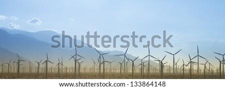 Windmill Farm Silhouette With Mountains - stock photo
