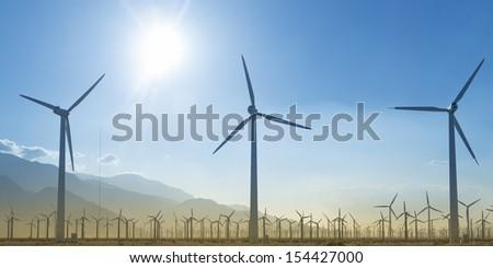 Windmill Farm Silhouette With Setting Sun - stock photo