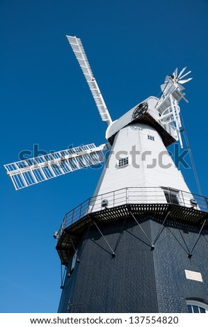 windmill filling the frame with a bright blue sky - stock photo