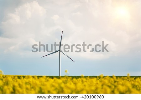 windmill for electric power prodaction on rural floral field - stock photo