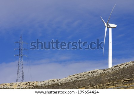 Windmill for renewable electric energy production and pylon, Teruel province, Aragon, Spain - stock photo