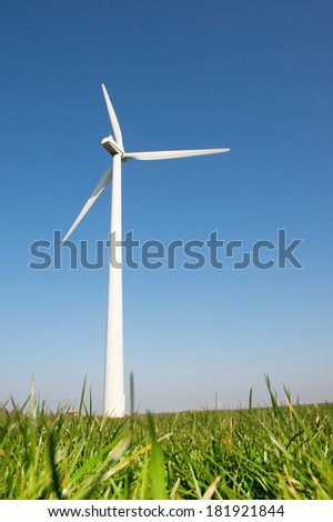 Windmill for wind energy in grass field - stock photo