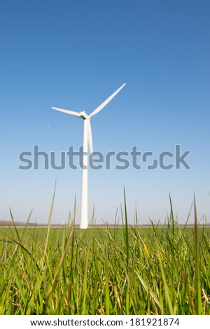 Windmill for wind energy with focus on grass - stock photo