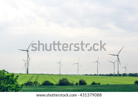 Windmill generator in wide yard. Group of eco windmills for renewable electric energy production.Windmills for electric eco power production. - stock photo