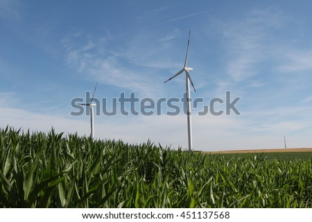 Windmill generator in wide yard / Yard of windmill power generatorunder blue sky, shown as energy industry concept.