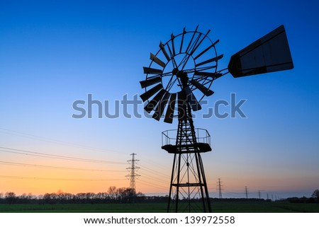 Windmill in a dutch landscape at sunset - stock photo