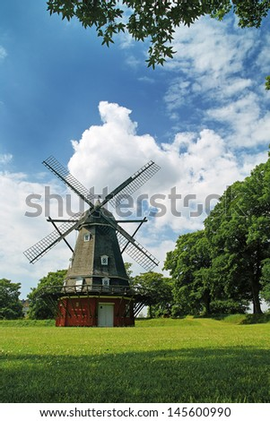 Windmill in a park on a bright sunny day with blue skies and white clouds in Copenhagen, Denmark