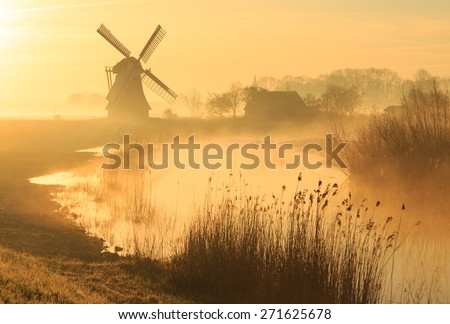 Windmill in a wetland during a foggy, yellow sunrise in the countryside.