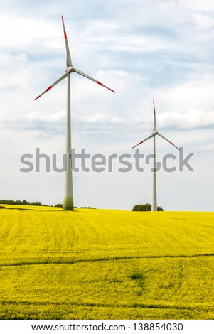 Windmill in blooming canola field - stock photo
