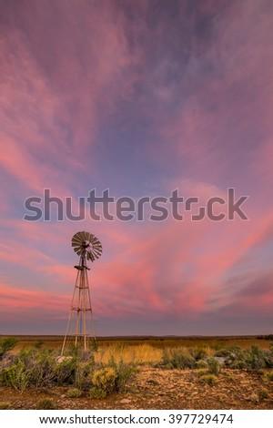 windmill in karoo at sunset - stock photo