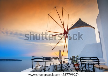 Windmill in Oia town at sunset. Santorini island, Greece. Beautiful landscape with sea view - stock photo