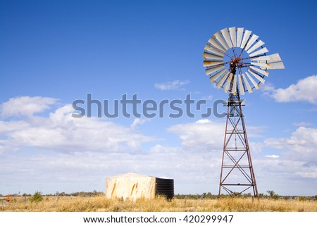 Windmill in Queensland, Australia, with blue sky and fluffy white clouds