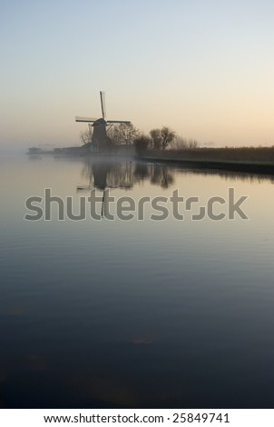 Windmill in the foggy morning - stock photo