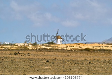 Windmill in the gaunt countryside blurred with hot summer haze - stock photo